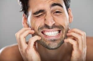 Man itching his beard while trying to grow a beard